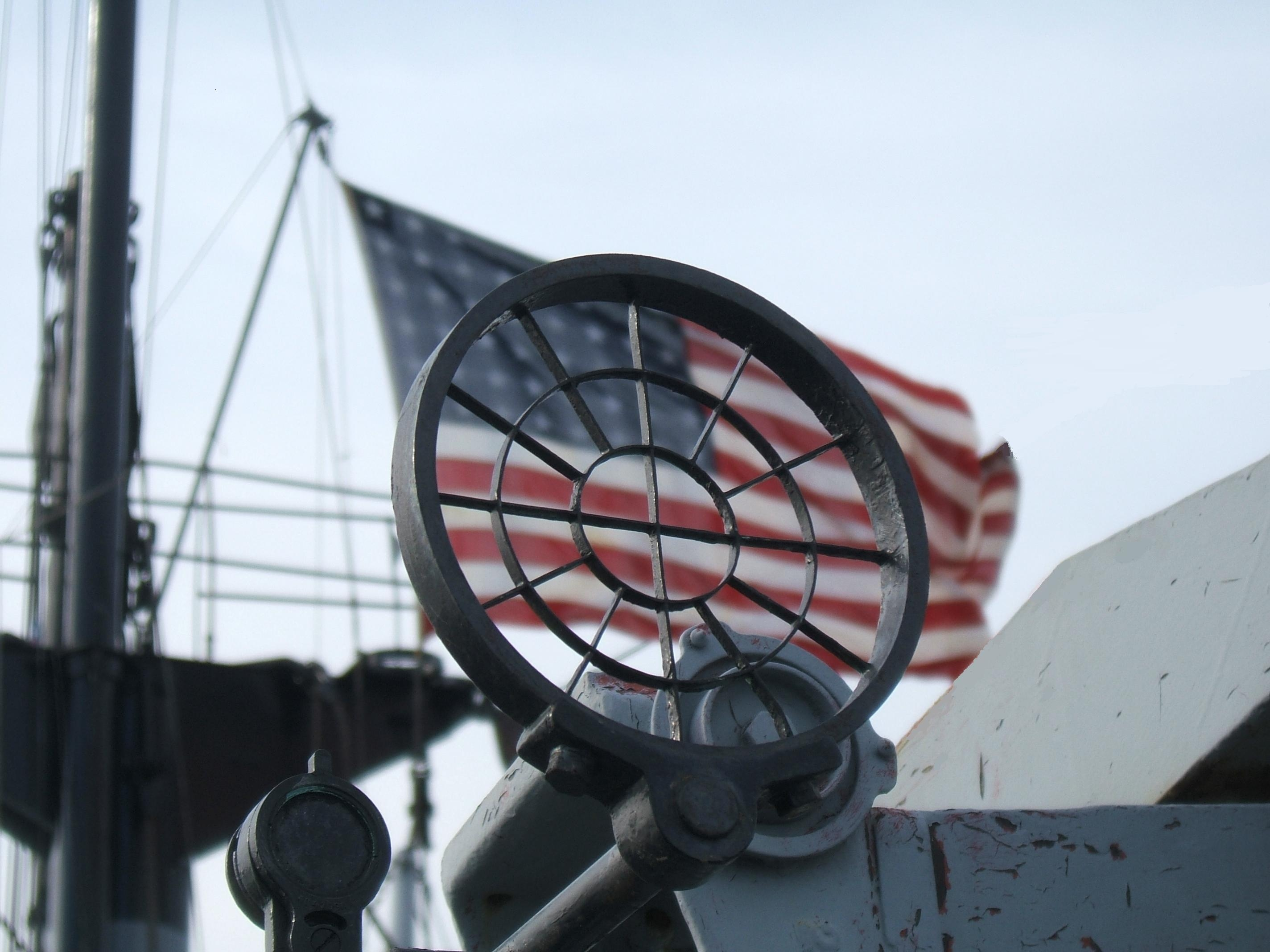 photograph of gunsight with u.s. flag in background